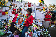 South Africans pose for photographs outside the Medic-Clinic Heart hospital where Nelson Mandela is being treated, in Pretoria, South Africa.