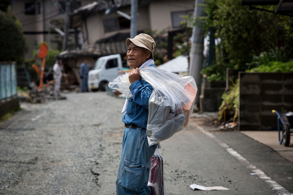 KUMAMOTO, JAPAN - APRIL 22: Earthquake survivors return home to get whatever they can still use on early morning of Friday April 22, 2016 in Mashiki Town, Kumamoto, Japan. To date 48 people are confirmed dead and more than 80,000 people have evacuated after an 6.5 earthquake on Thursday night and a stronger 7.3 quake on Saturday morning struck the Kyushu Island in western Japan.<br /> <br /> Photo: Richard Atrero de Guzman