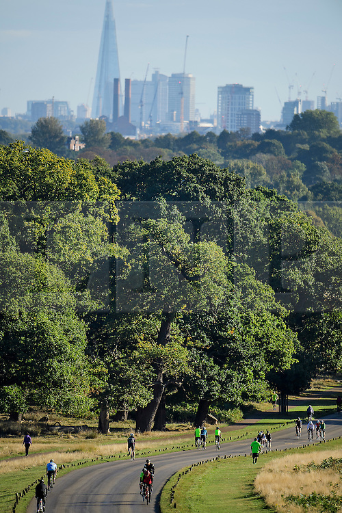 © Licensed to London News Pictures. 09/10/2016. London, UK. Cyclists and joggers make their way through Richmond Park on an autumnal morning, with the city scape of London in the background. Photo credit: Ben Cawthra/LNP