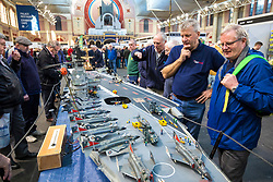 19/01/2018. London, UK. Dave Fortey (2-R) talks with a visitor about his model of HMS Ark Royal (R09) at the London Model Engineering Exhibition at Alexandra Palace. Fortey, a former Royal Navy mechanic and sub-lieutenant, built the model over 25 years. It is the first time it has been put on display to the public. Photo credit: Rob Pinney