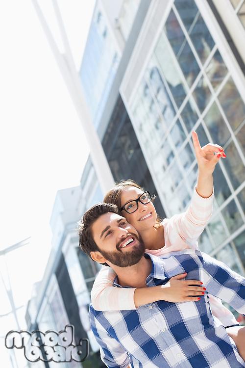 Happy woman showing something to man while enjoying piggyback ride in city