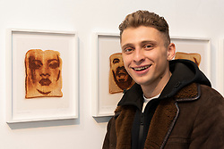 "© Licensed to London News Pictures. 06/06/2019. London, UK. 22 year old artist, model and skateboarder Blondey with his artwork featuring singer Rihanna titled ""Since Sliced Bread"" 2019. The work is part of Epiphanies featuring the famous faces of a series of 25 laser etched portraits on toast showing at The Ronchini Gallery. Photo credit: Ray Tang/LNP"