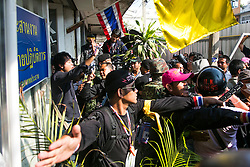© Licensed to London News Pictures. 17/01/2014. Anti-Government Protestors push back crowds from the alleged apartment of the suspects whom threw an explosive device injuring eight people during an anti-government street rally on January 17, 2014 in Bangkok, Thailand. Anti-government protesters launch 'Bangkok Shutdown', blocking major intersections in the heart of the capital, as part of their bid to oust the government of Prime Minister Yingluck Shinawatra ahead of elections scheduled to take place on February 2. Photo credit : Asanka Brendon Ratnayake/LNP