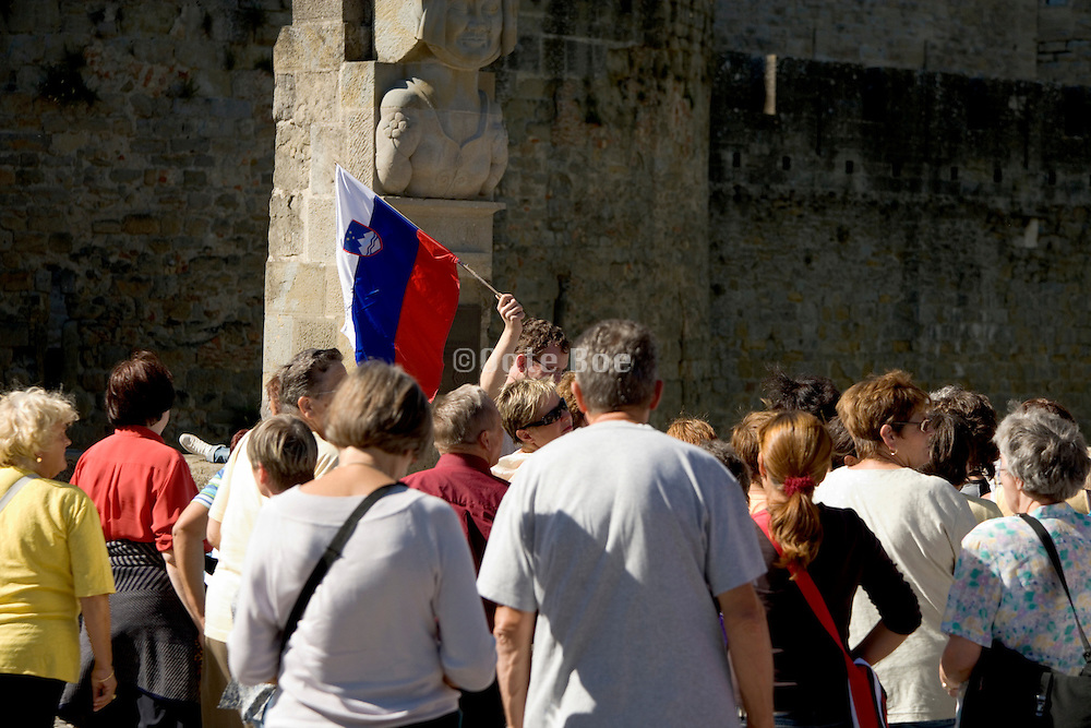 people swarming around a tourist guide in a medieval town Europe France
