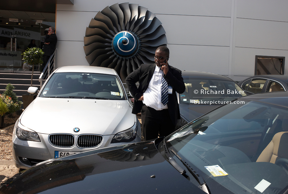 A male chauffeur of African-descent makes a mobile telephone call at the Rolls-Royce chalet at the Paris Air Show exhibition