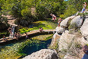 People jumping off the rocks that surround, Jacobs Well Natural Area, a Hayes County Park, Texas.