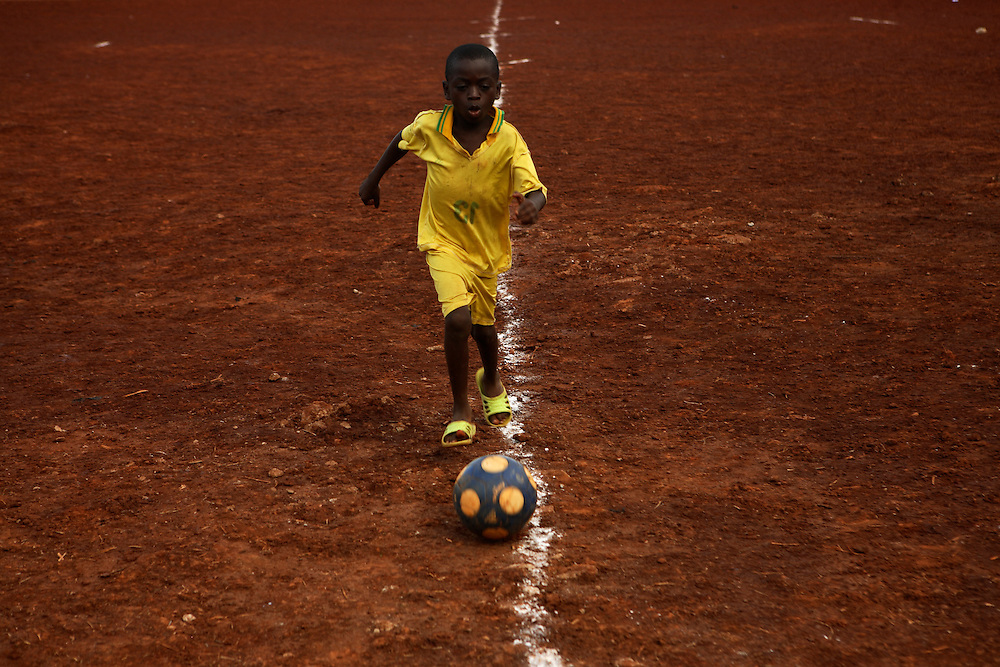 A boy plays with a football in half time of a game on Cite Verte field. Yaounde, Cameroon.