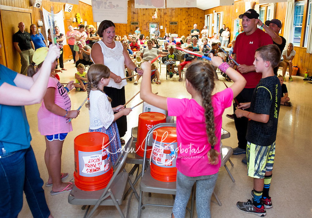 """Children and their parents join together on stage for a performance of Lakes Region Child Care Services' """"Youth Beatz"""" with Mr. Rich at the Leavitt Park Clubhouse on Tuesday evening. (Karen Bobotas/for the Laconia Daily Sun)"""