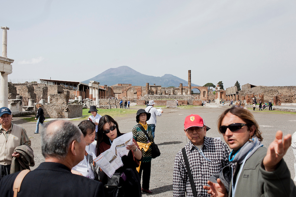 POMPEII, ITALY - 4 APRIL 2013:    A guide introduces tourists to the forum, the city's main square, dating the 2nd century BC, in Pompeii, Italy, on April 4th, 2013. Located at the intersection between the two main streets of the original urban center, the Forum was the city's main square, surrounded on all sides by religious, political, and business buildings.<br /> <br /> In recent years, a series of collapses at the site have alarmed conservationists, who warn that the ancient Roman city is dangerously exposed to the elements ? and poorly served by the red tape, lack of strategic planning and limited personnel of the site's historically troubled management. <br /> <br /> Pompeii, along with Herculaneum, was buried under 4 to 6 meters (13 to 20 ft) of ash and pumice in the eruption of Mount Vesuvius in 79 AD. After its initial discovery in 1599, Pompeii was rediscovered as the result of intentional excavations in 1748 by the Spanish military engineer Rocque Joaquin de Alcubierre.<br /> <br /> Pompeii is an UNESCO World Heritage Site and one of the most popular tourist attractions of Italy, with approximately 2.5 million visitors every year.<br /> <br /> Gianni Cipriano for The New York Times