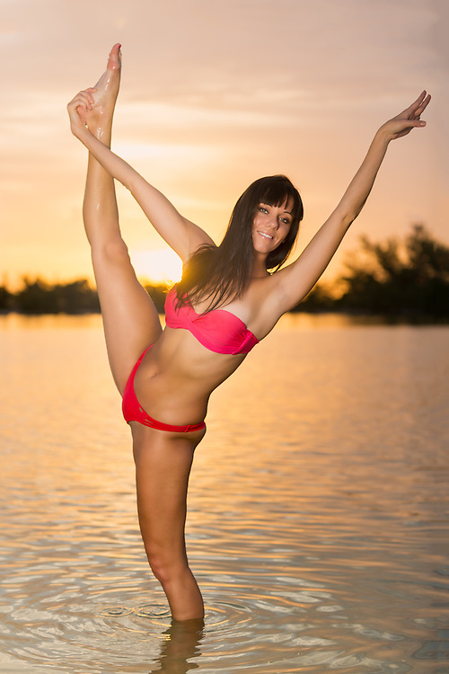 Young woman practicing yoga early morning in the beach, very happy and joyful