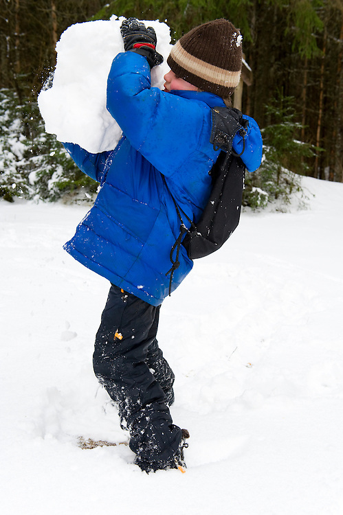 Estonian boy with a snow ball in the forest