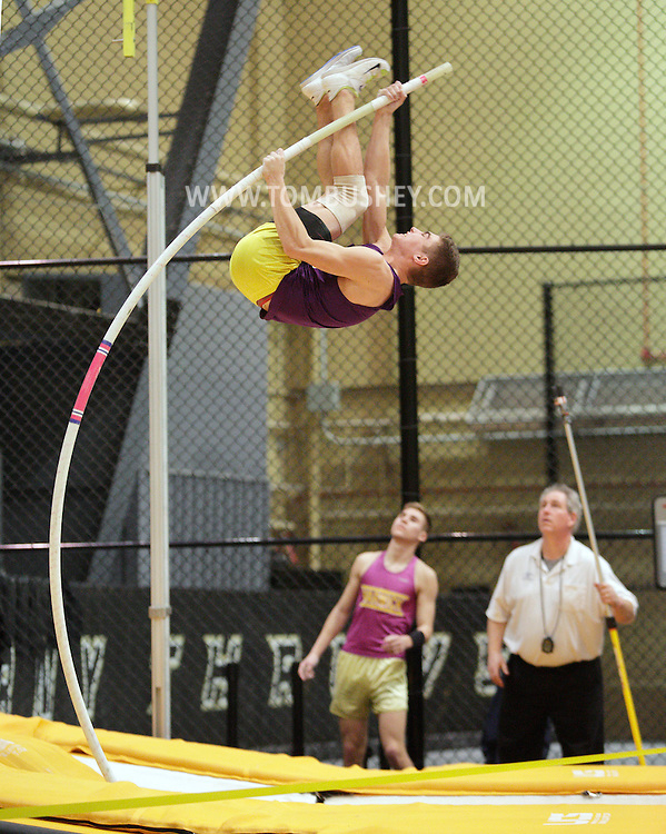 Warwick's Derek Dibona pole vaults as his teammate Todd Uckermark, in background at left, looks on during the Section 9 indoor track state qualifying meet at West Point  on Friday, Feb. 22, 2013. Uckermark won the event, and Dibona finished third. Uckermark, Dibona and Ellenville's Justin Farrenkopf, who finished second, all qualified for the state meet.
