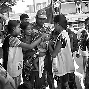 At the Jogbani border crossing between India and Nepal. a transit team assisted by an Indian army jawan vaccinate children as Nepali border police women look on. Transit teams are deployed at strategic locations including international borders to reach mobile and migrant populaitons.