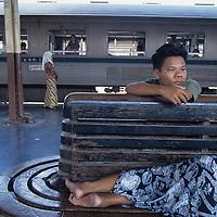 Thailand, Bangkok, Man rests on bench at Bangkok Train Station