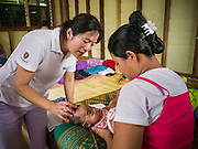21 MAY 2013 - MAE KU, TAK, THAILAND:  Dr. CINDY CHU, an American physician, examines a child at the SMRU clinic in Mae Ku. Health professionals are seeing increasing evidence of malaria resistant to artemisinin coming out of the jungles of Southeast Asia. Artemisinin has been the first choice for battling malaria in Southeast Asia for 20 years. In recent years though,  health care workers in Cambodia and Myanmar (Burma) are seeing signs that the malaria parasite is becoming resistant to artemisinin. Scientists who study malaria are concerned that history could repeat itself because chloroquine, an effective malaria treatment until the 1990s, first lost its effectiveness in Cambodia and Burma before spreading to Africa, which led to a spike in deaths there. Doctors at the Shaklo Malaria Research Unit (SMRU), which studies malaria along the Thai Burma border, are worried that artemisinin resistance is growing at a rapid pace. Dr. Aung Pyae Phyo, a Burmese physician at a SMRU clinic just a few meters from the Burmese border, said that in 2009, 90 percent of patients were cured with artemisinin, but in 2010, it dropped to about 70 percent and is now between 55 and 60 percent. He said the concern is that as it becomes more difficult to clear the parasite from a patient, progress that has been made in combating malaria will be lost and the disease could make a comeback in Southeast Asia.  PHOTO BY JACK KURTZ