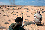 Smoke rises on the horizon as frontline Libyan rebel fighters advance during a battle with pro-Qaddafi forces just outside the coastal town of Bin Jawwad. Rebels fought pro-Qaddafi forces there throughout the day as they tried to regain control the town from government forces that seized the town overnight.