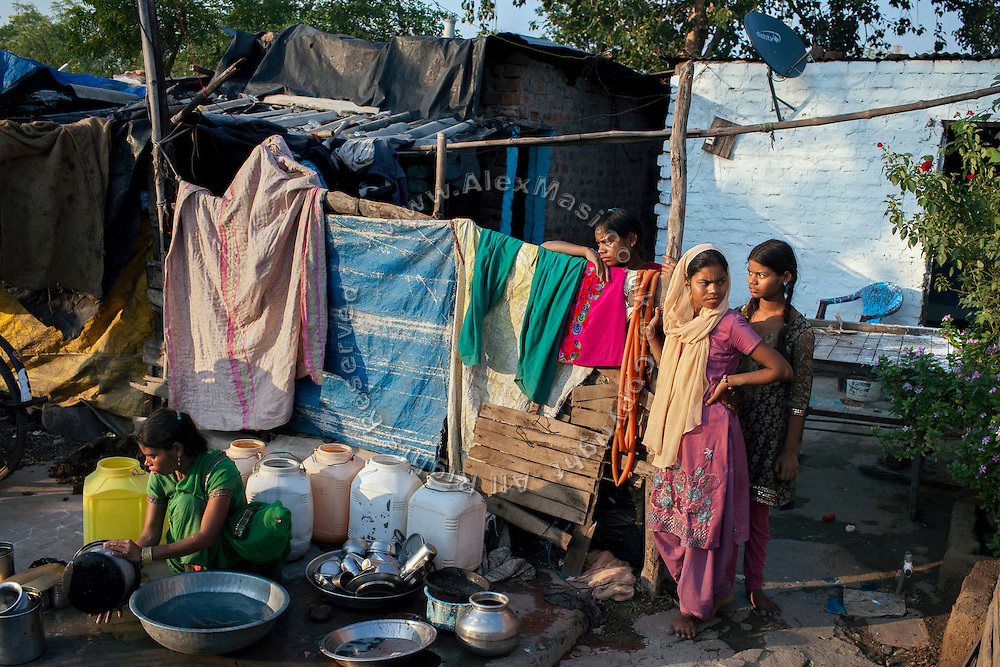 (right to left) Poonam, 12, is standing next to her sisters Arti, 18, and Jyoti, 13, while their mother is washing dishes in front of their newly built home in Oriya Basti, one of the water-contaminated colonies in Bhopal, central India, near the abandoned Union Carbide (now DOW Chemical) industrial complex, site of the infamous '1984 Gas Disaster'.