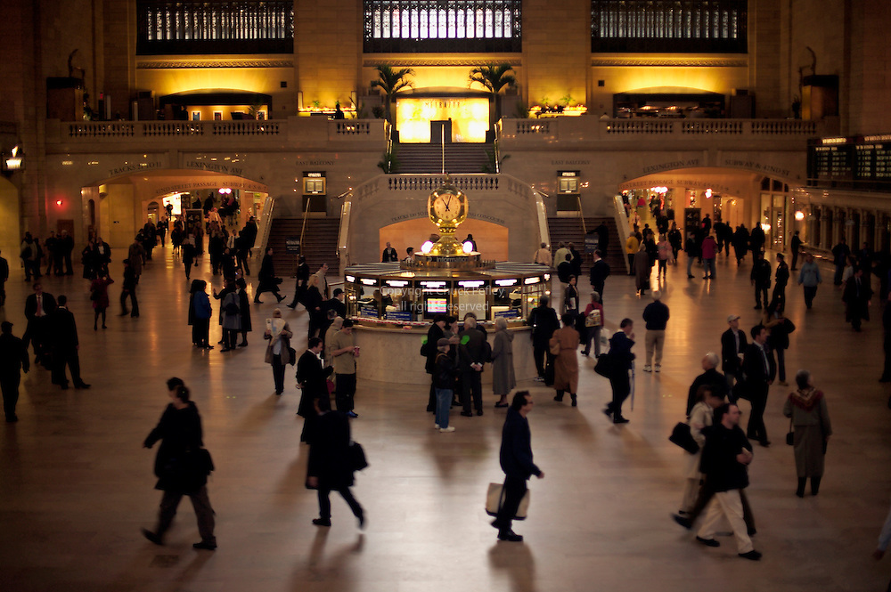 People crossing grand hall with gold clock and train information booth in center at Grand Central Station, Midtown Manhattan, New York, NY