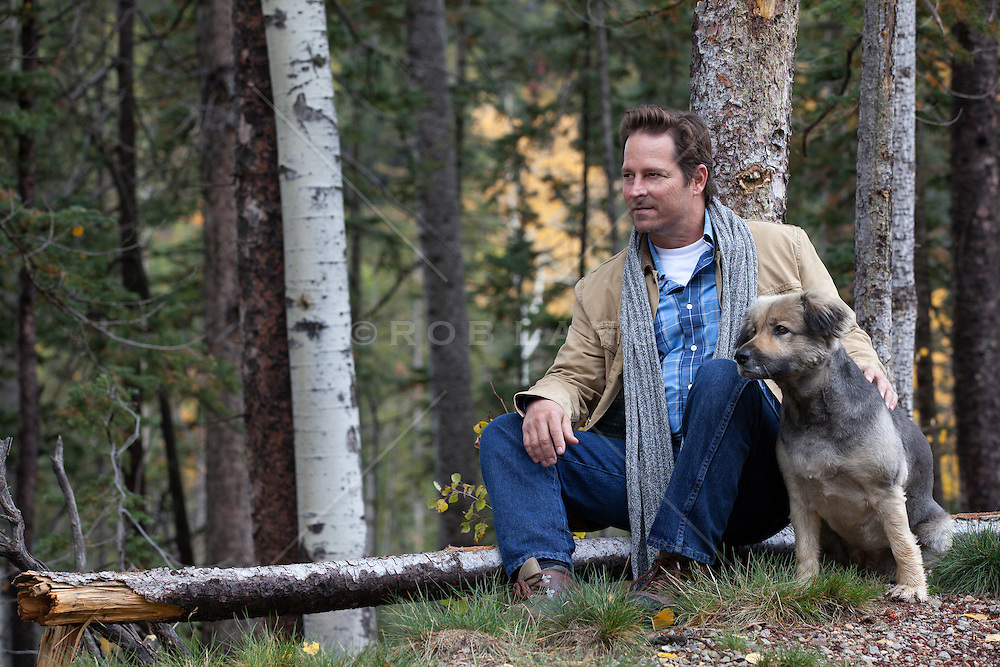 man enjoying time in the woods with his dog