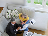 Woman sitting on sofa with financial advisor elevated view