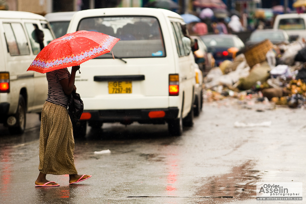 A woman holding an umbrella crosses a street in central Accra, Ghana on Tuesday June 16, 2009.