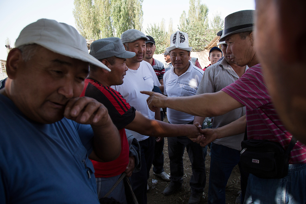Kyrgyz farmers shake on a deal to sell livestock at the stockyards in Ala Buka.