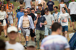 Image ©Licensed to i-Images Picture Agency . 20/07/2014 . Henham Park , Suffolk , United Kingdom . Wellies out - festival goers walk through the campsite to the festival . The Latitude Festival of music and arts . Picture by Joel Goodman/i-Images