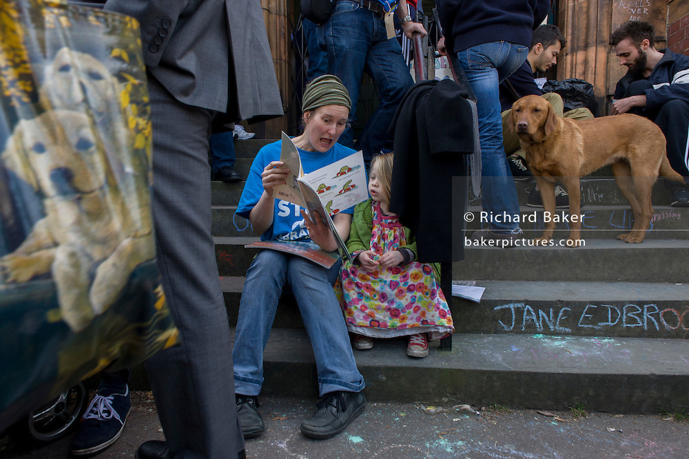 Artist Megan Roberts reads to a friend's daughter on the steps of the closed Carnegie Library, in Herne Hill, south London on 2nd April 2016. The angry local community in the south London borough have occupied their important resource for learning and social hub for the weekend. After a long campaign by locals, Lambeth have gone ahead and closed the library's doors for the last time because they say, cuts to their budget mean millions must be saved. A gym will replace the working library and while some of the 20,000 books on shelves will remain, no librarians will be present to administer it. London borough's budget cuts mean four of its 10 libraries will either close, move or be run by volunteers.