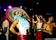 Male clubber wearing a very large colourful hat and feather boa Ibiza 1999