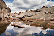 Storm clouds are reflected in the still waters of Chasm Lake in Rocky Mountain National Park in Colorado.
