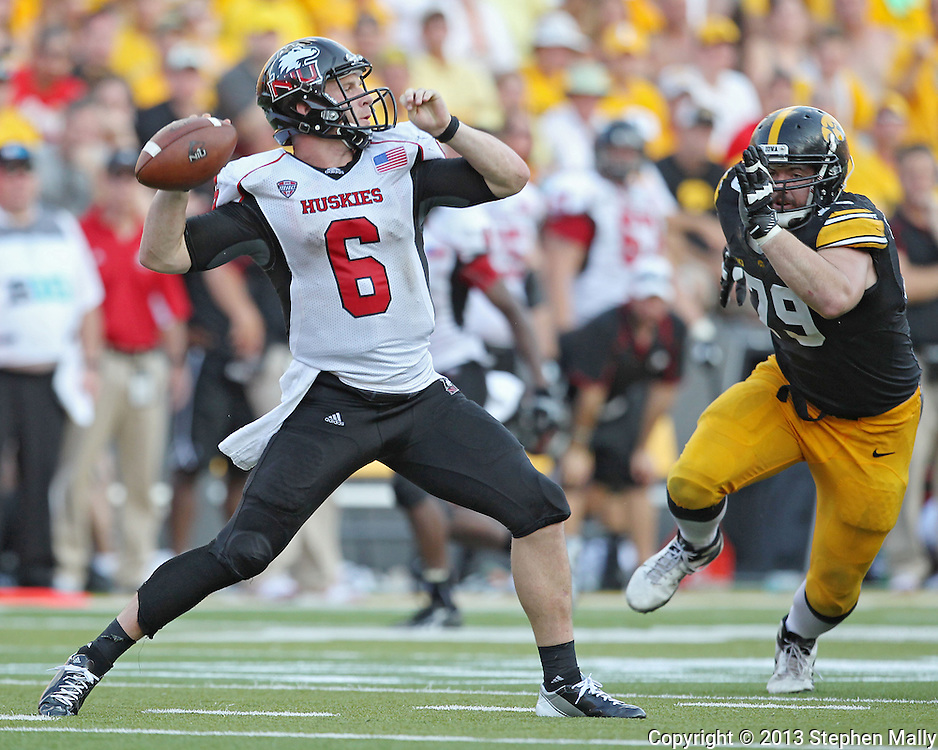 August 31 2013: Northern Illinois Huskies quarterback Jordan Lynch (6) loads to throw as Iowa Hawkeyes defensive lineman Dominic Alvis (79) closes in during the second half of the NCAA football game between the Northern Illinois Huskies and the Iowa Hawkeyes at Kinnick Stadium in Iowa City, Iowa on August 31, 2013. Northern Illinois defeated Iowa 30-27.