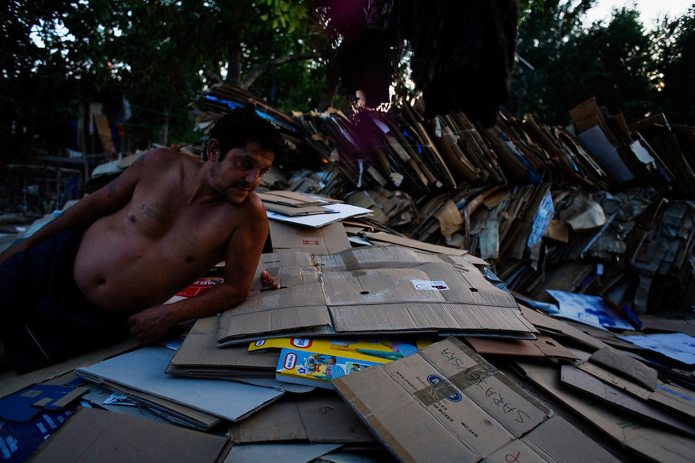 A man lounges on his friend Bruce Lee's collection of cardboard, which he collected from around Belgrade to sell to recyclers. Stara Gazela.