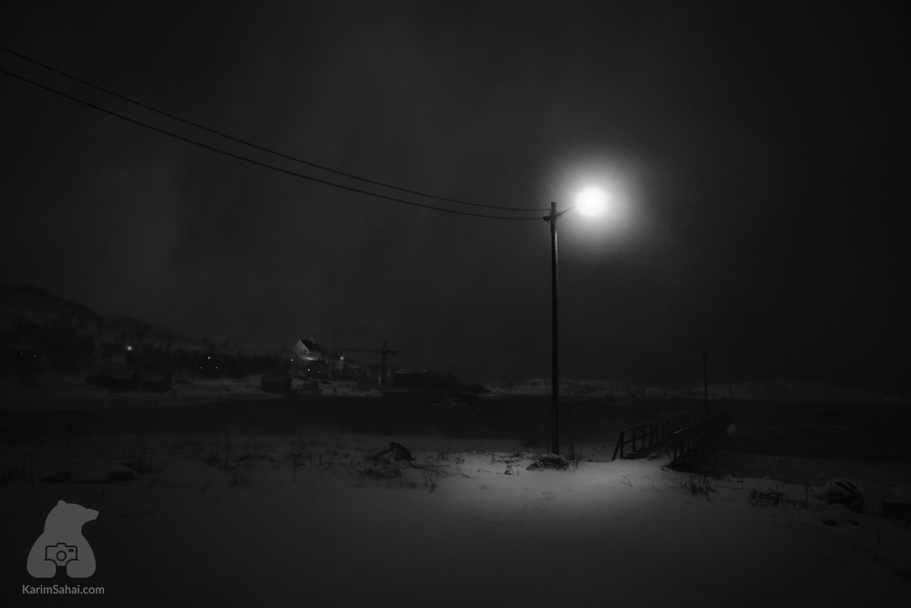 A lone street light provides a dim illumination on a dark arctic winter day in Bergsfjord, Finnmark, Norway