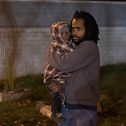 Frank Littleton of Minneapolis holds his nephew at a gathering of Black Lives Matter protest outside the Minneapolis Police Department 4th precinct headquarters on Thursday, November 19, 2015 in Minneapolis, Minnesota. <br /> <br /> Protests and an encampment at the site have been ongoing since the police shooting of 24-year-old Jamar Clark by Minneapolis Police on Sunday, November 15. Due to work and school commitments, it was Littleton's first opportunity to visit the site. <br /> <br /> A more mellow and festive atmosphere, with a smaller police presence, prevailed after Wednesday evening's tear gas clashes between police and protesters. <br /> <br /> <br /> Photo by Angela Jimenez for Minnesota Public Radio www.angelajimenezphotography.com
