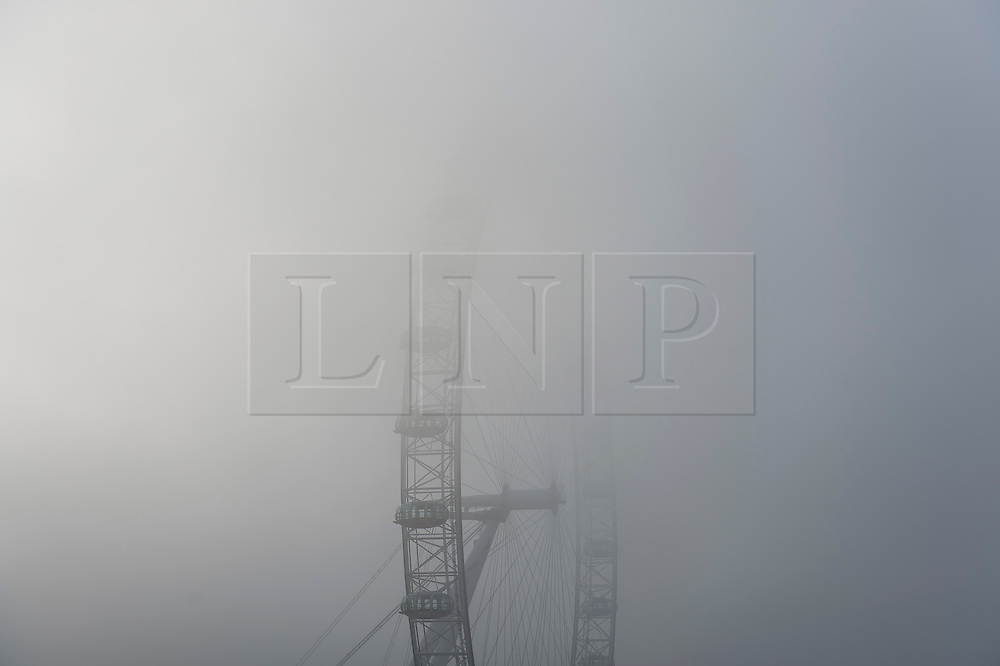 © Licensed to London News Pictures. 01/11/2015. London, UK.  Fog covering the London Eye next to the River Thames in Westminster on an early autumn morning.  Photo credit: Ben Cawthra/LNP