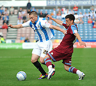 Picture by Graham Crowther/Focus Images Ltd. 07763140036.10/9/11 .Donal McDermott of Huddersfield is stopped by Dave Buchanan of Tranmere during the Npower League 1 game at the Galpharm Stadium, Huddersfield.