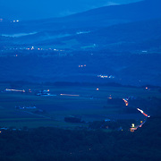 Traffic along the scenic Route 230 in Lake Toya as the inky blue blanket of night falls over the landscape.