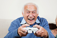 Portrait of excited elderly man playing video game at home