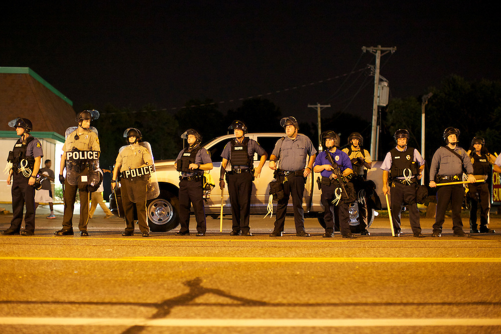 Police officers, many in riot gear, begin to line West Florissant Avenue in an attempt to break up the growing crowd of demonstrators. Protests have been ongoing in Ferguson, Missouri since the shooting death of Michael Brown, the eighteen-year-old unarmed teen killed by police on August 9, 2014.