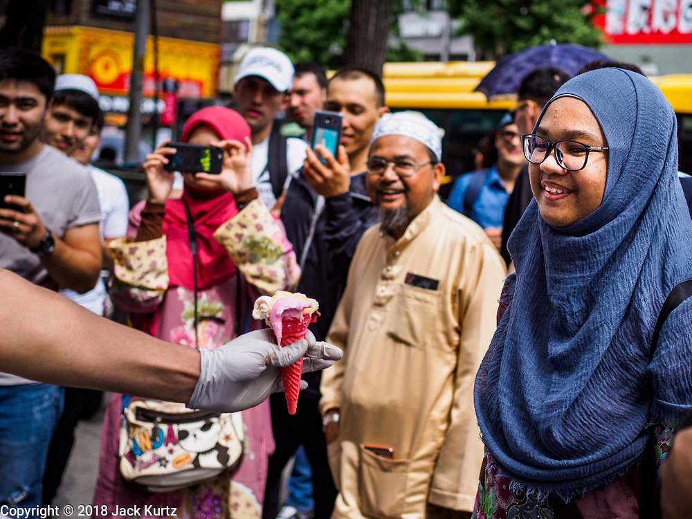 15 JUNE 2018 - SEOUL, SOUTH KOREA: A Muslim woman buys a Turkish ice cream on Itaewon Street near Seoul Central Mosque on Eid al Fitr, the Muslim Holy Day that marks the end of the Holy Month of Ramadan. There are fewer than 100,000 Korean Muslims, but there is a large community of Muslim immigrants in South Korea, most in Seoul. Thousands of people attend Eid services at Seoul Central Mosque, the largest mosque in South Korea.    PHOTO BY JACK KURTZ