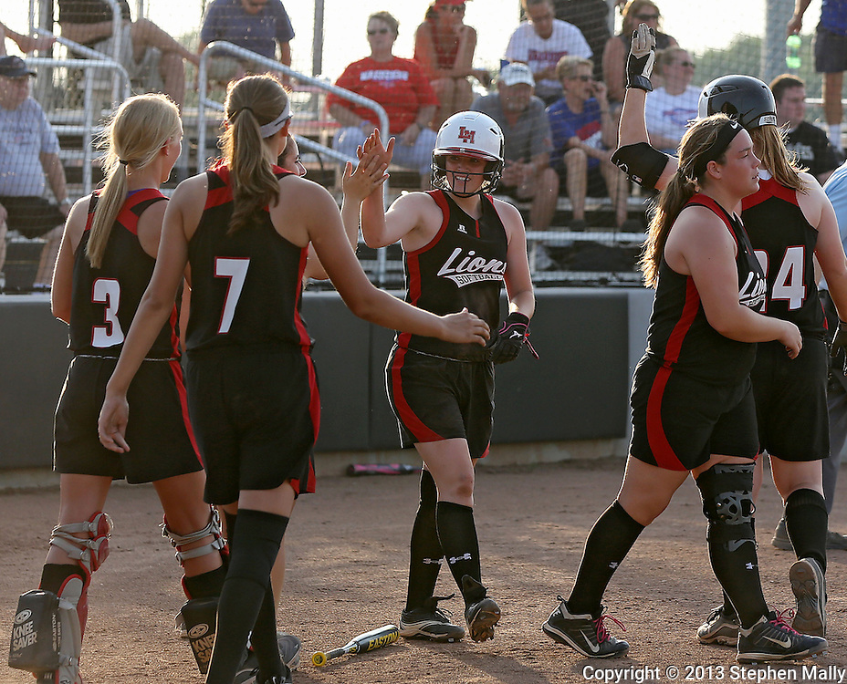 Linn-Mar's Maddy Ryan (2) celebrates with her team after scoring the winning run in the bottom of the 9th inning during the softball game between Cedar Rapids Washington and Linn-Mar at Oak Ridge Middle School in Marion on Thursday, June 20, 2013. The Lions defeated the Warriors 7-6 in 9 innings.
