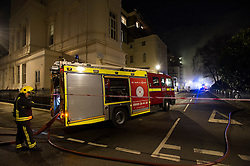 © London News Pictures. 21/01/2014. London, UK. Fire crews and other emergency services at the scene of a fire at a £3 million property on Hyde Park Gardens Muse, one of the most expensive street in London. The grade 2 listed building was gutted by a fire that started in the basement. Eight fire engines and 58 firefighters and officers attended the scene. There have been no reports of injuries. Photo credit: Ben Cawthra/LNP