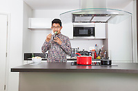 Young man eating broccoli at kitchen counter in home