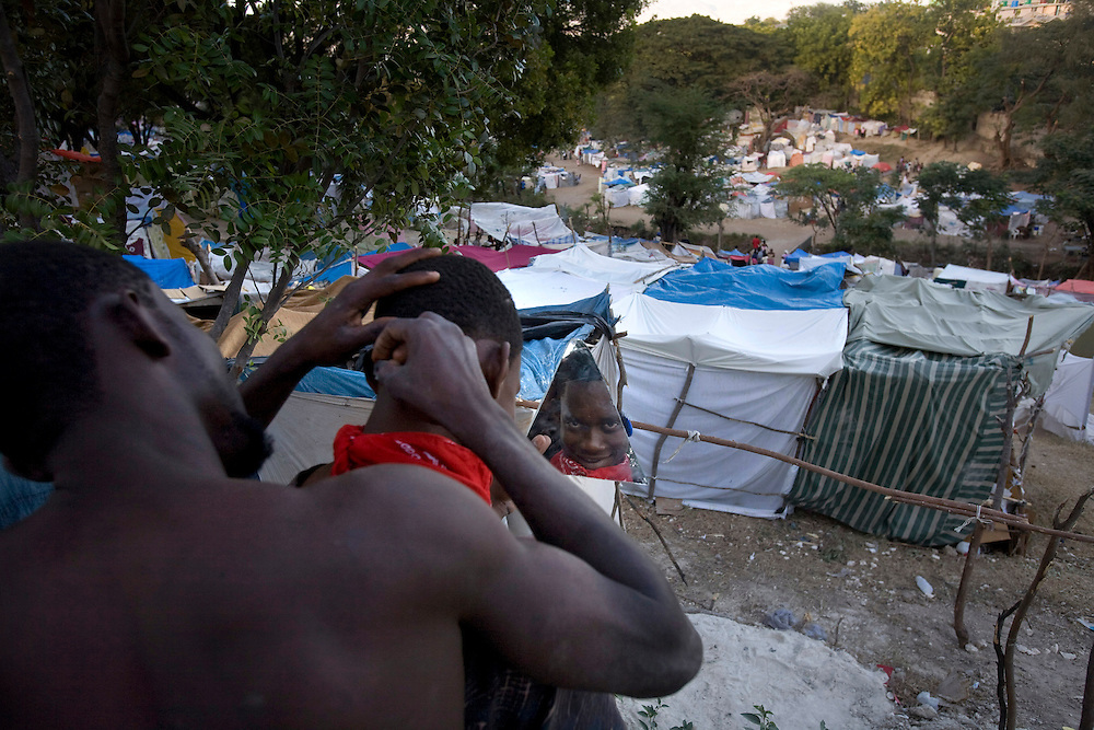 A man giving a  haircut in a refugee camp that opened, after the 7.0 earthquake, on a golf field in Port Au prince, on January 30, 2010.