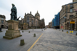 Edinburgh, Scotland, UK. 24 March, 2020.  Deserted streets in the heart of the Old Town tourist district in Edinburgh. All shops and restaurants are closed with very few people venturing outside following the Government imposed lockdown today. Pictured; Statue of Adam Smith and St Giles cathedral on an empty Royal Mile. Iain Masterton/Alamy Live News