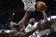 April 09, 2012; Indianapolis, IN, USA; Indiana Pacers shooting guard Paul George (24) tries to put up the shot against heavy pressure from Toronto Raptors power forward Amir Johnson (15) at Bankers Life Fieldhouse. Indiana defeated Toronto 103-98. Mandatory credit: Michael Hickey-US PRESSWIRE