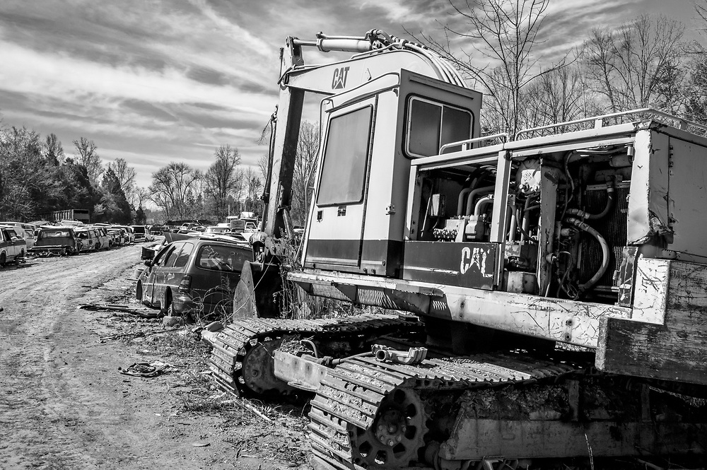 A retired excavator takes its place among the junked cars & trucks in the auto graveyard. The bright outline & cab complements the vanishing road and dramatic sky background. Emulated to look like an image printed from Agfa APX 100 B&w film, the image pics up a small amount of contrast and film grain character.