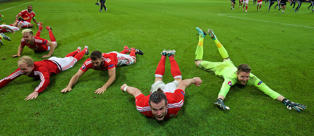 LILLE, FRANCE - Friday, July 1, 2016: Wales' Joe Ledley, Gareth Bale and goalkeeper Wayne Hennessey slide on the pitch as they celebrate a 3-1 victory over Belgium and reaching the Semi-Final during the UEFA Euro 2016 Championship Quarter-Final match at the Stade Pierre Mauroy. (Pic by David Rawcliffe/Propaganda)