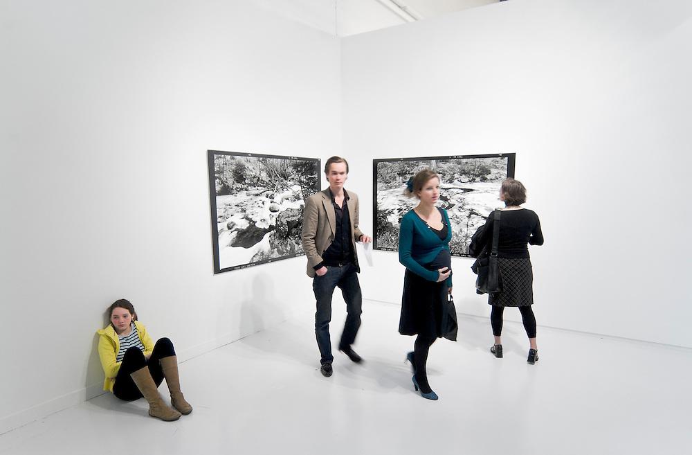 Nederland, Den Bosch, 20080126.<br /> Meisje zit op de grond naast twee uitvergrote foto's. Andere volwassenen staan te kijken.<br /> Opstelling in SM's in het Stedelijk Museum in Den Bosch.<br /> Het 'laboratorium voor de dingen'. Dat is een eenvoudig gebouwtje dat op verscheidene plaatsen te zien is geweest. Hier worden keer op keer nieuwe objecten binnengebracht, waarmee de ruimte per locatie getransformeerd wordt tot een nieuwe installatie. Naast deze nieuwe versie van de inrichting van het laboratorium zullen ook nieuwe foto's en dubbelweefsels (die in samenwerking met het textielmuseum zijn gemaakt) gepresenteerd worden. Het werk van Frans Beerens is moeilijk te positioneren. Het betreft een krachtig realisme, maar anderzijds lijkt het werk juist mystiek en ongrijpbaar. Juist in deze suggestieve verwijzingen schuilt een mysterie en dat maakt het werk van Beerens aantrekkelijk.