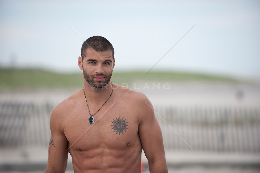 shirtless man with shaved head and tattoo at the beach